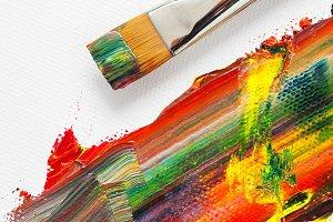 Paintbrush and mixed rainbow paints