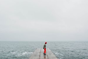 Girl on the concrete at winter sea