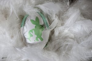 Green and white eggs on feather back