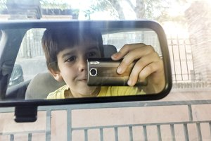 Child taking picture with phone.