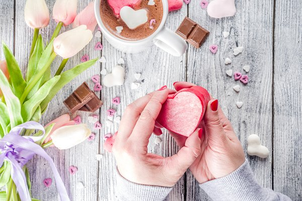 Girl hands hold Valentines gift box
