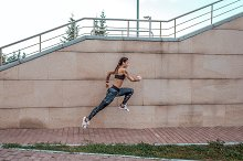 Girl athlete runs in a jump. In city by  in Sports