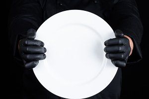 Chef in black uniform  holding plate