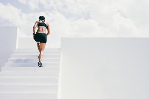 Fitness woman running up the stairs