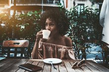Cute biracial female drinking coffee by  in People