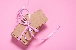 Cardboard gift box with tag on pink