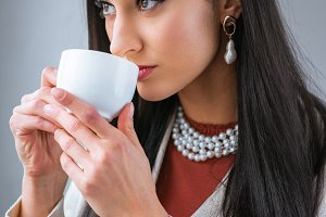 elegant young woman drinking coffee