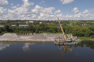 River crane excavator on barge.