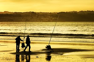 fishermen in the beach at dusk