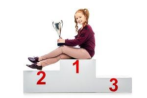 happy schoolgirl sitting on winner p