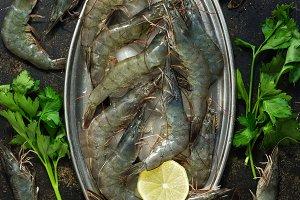 Raw tiger prawns on a metal plate wi