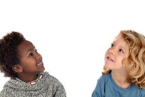 Two happy children looking up