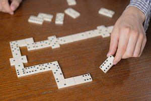 close up hand hold domino piece on w