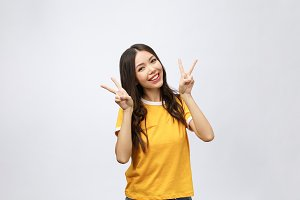 Happy young asian woman showing two