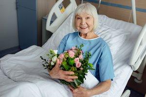 happy recovering senior woman lying