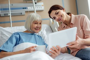 happy senior woman and daughter usin