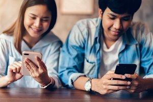 Friends using smartphone on cafe, Du