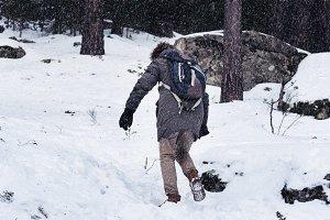 Woman walking in the snowed mountain