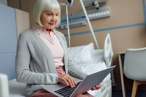 senior woman sitting on bed and usin