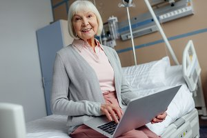 smiling senior woman sitting on bed