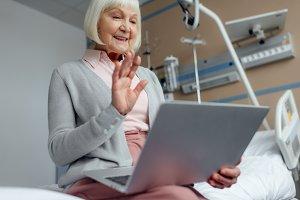 happy senior woman sitting on bed, u