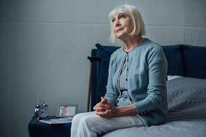 pensive senior woman sitting on bed