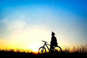 Silhouette of girl with bicycle