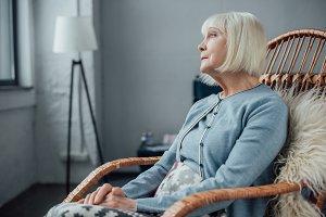 senior woman sitting in wicker rocki