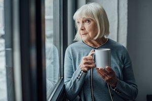 senior woman sitting near window and