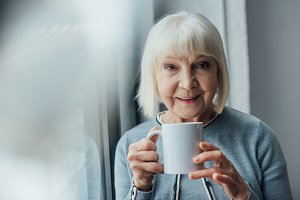 smiling senior woman holding cup of