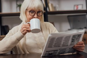 senior woman in glasses sitting at t