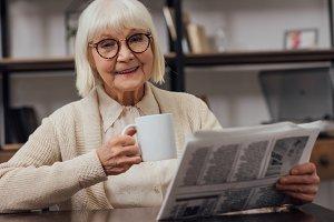 happy senior woman sitting at table