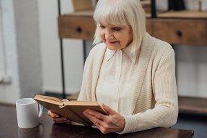 smiling senior woman sitting at tabl