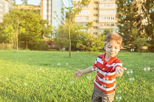 Happy boy playing with soap bubbles