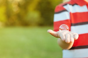 Boy showing soap bubble in his hand