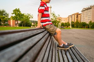 Boy sitting on the top of bench park