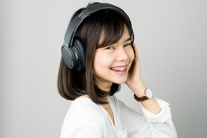 girl in white casual dress listening