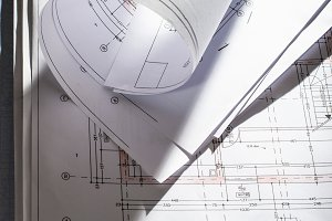 Blueprints on architect desk. Stacke
