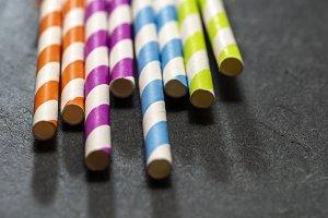 Multicoloured drink straws on dark s