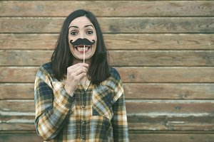 Funny young woman holding mustache