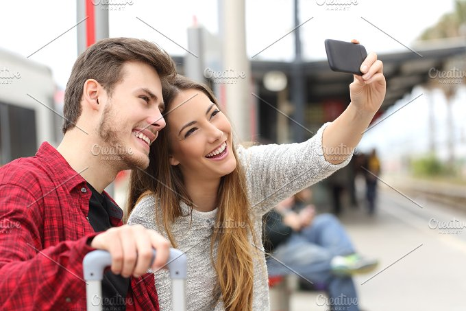 Couple of travelers photographing a selfie with a smartphone.jpg - Technology