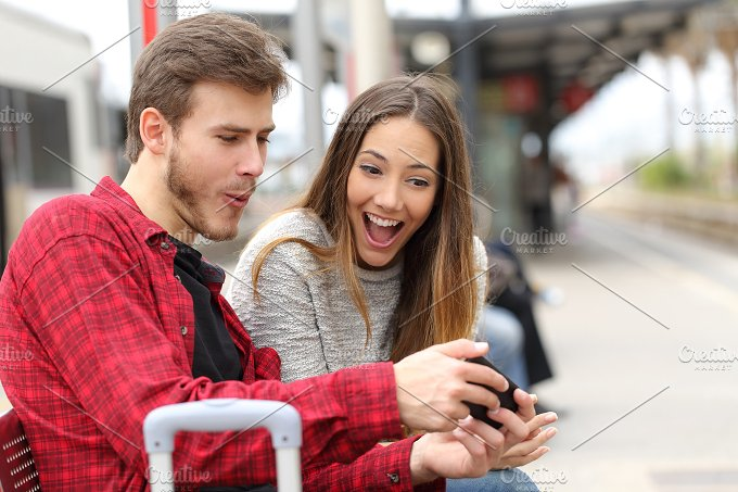 Couple playing games with a smart phone in a train station.jpg - Technology