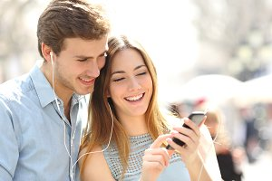 Couple sharing music from a smart phone on the street.jpg