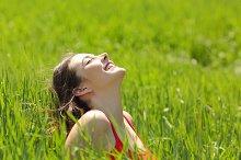 Happy girl face breathing fresh air in a meadow.jpg