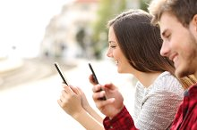 Teen couple using smart phones in a train station.jpg