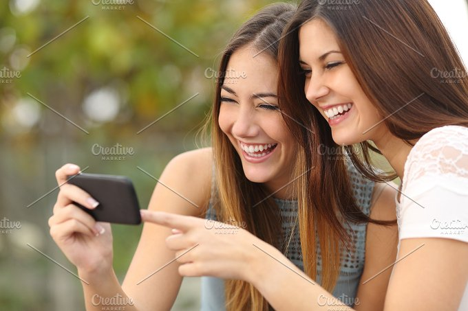 Two funny women friends laughing and sharing media in a smart phone .jpg - Technology