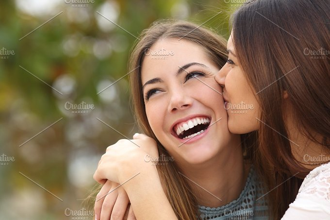 Woman laughing with perfect teeth while a friend is kissing her.jpg - People