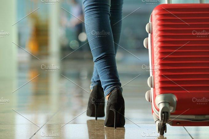 Traveler woman legs walking carrying a suitcase.jpg - Transportation