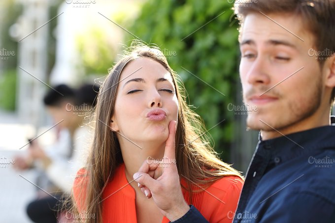 Woman trying to kiss a man and he is rejecting her.jpg - People