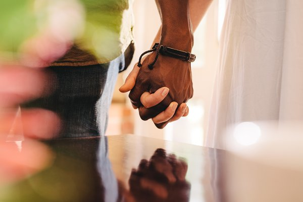Young man and woman holding hands.